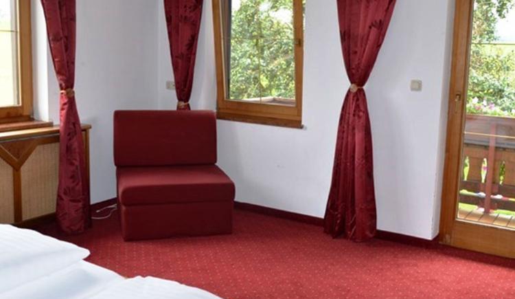 Schlafzimmer im Hintergrund ein gemütlicher Sessel und Fenster