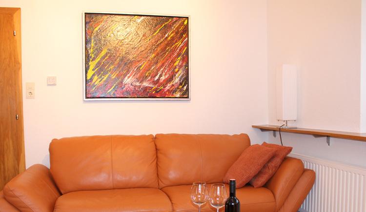 organe Ledercouch , auf der Wand dahinter ein modernes Gemälde