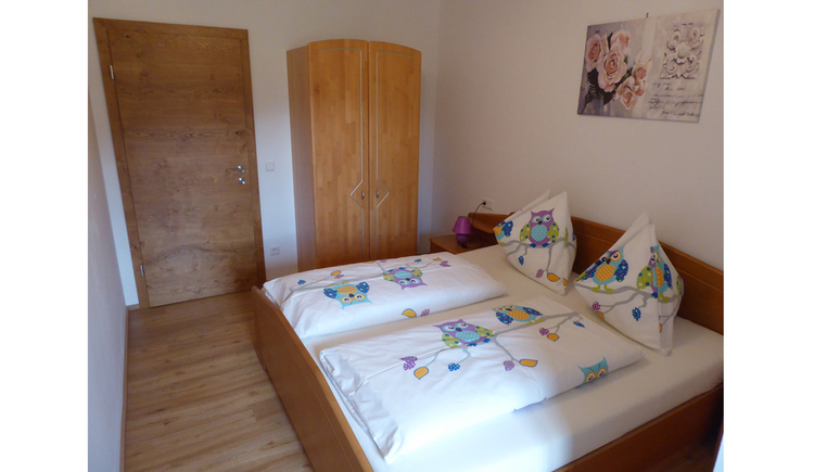 sleeping room with doublebed, wooden floor, on the backside the wardrobe and the door.