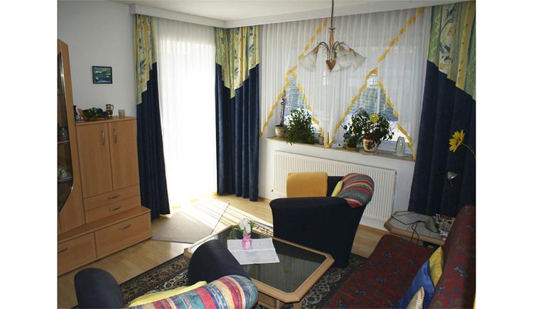 Wohnbereich mit Couch, Sessel, Tisch, Wohnwand, im Hintergrund eine Balkontür und Fenster