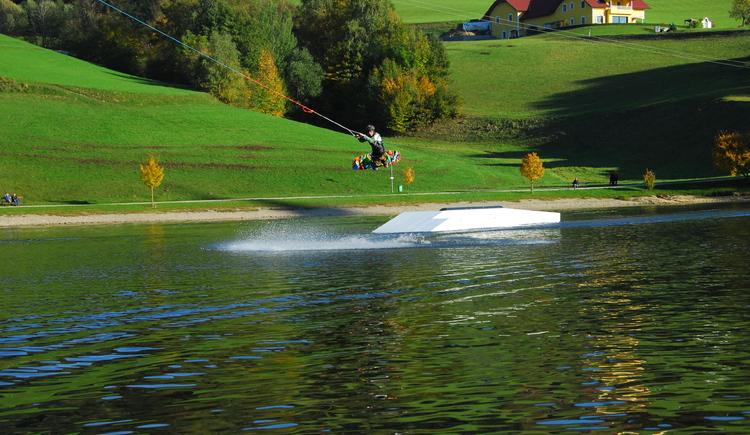 Wakeboardfahrer springt über eine Rampe am Wasserschilift Waldhausen