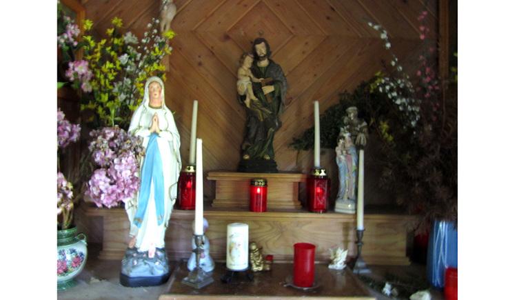 Blick auf Heiligenfiguren, Kerzen, Blumen seitlich