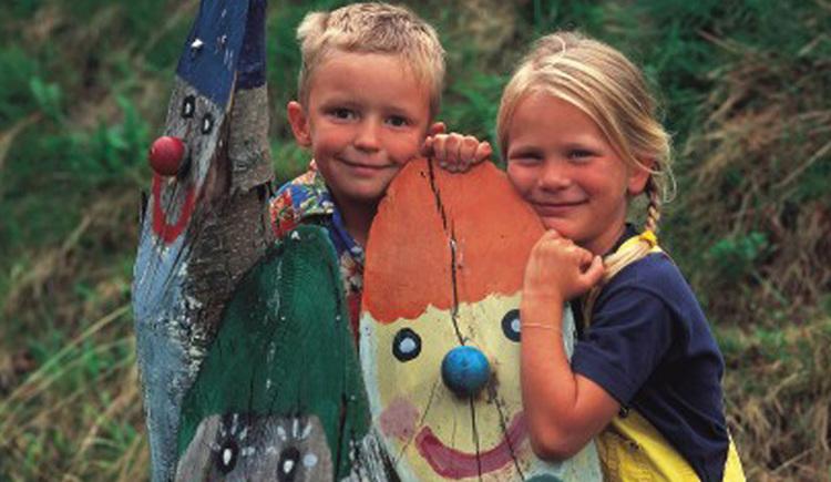 Kinder stehen neben den selbstbemalten Kolomandl (aus Holz)