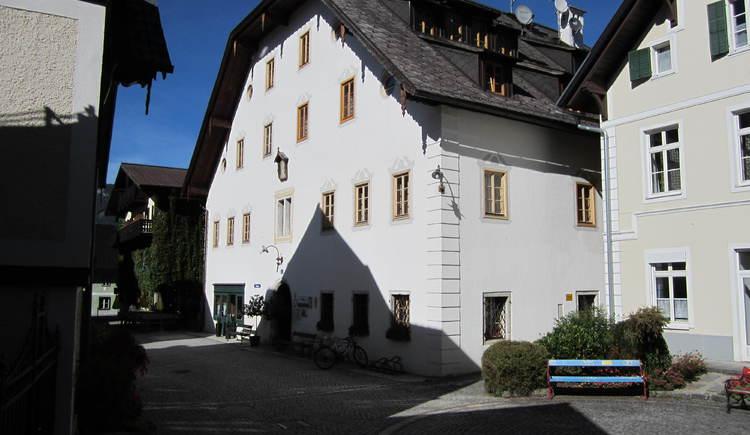Blick in die Kirchengasse zum Höplingerhaus mit Eingang zum Tourismusbüro und Frisör Da Hoarschneida. (© Ferienregion Dachstein Salzkammergut, Michaela Kefer)