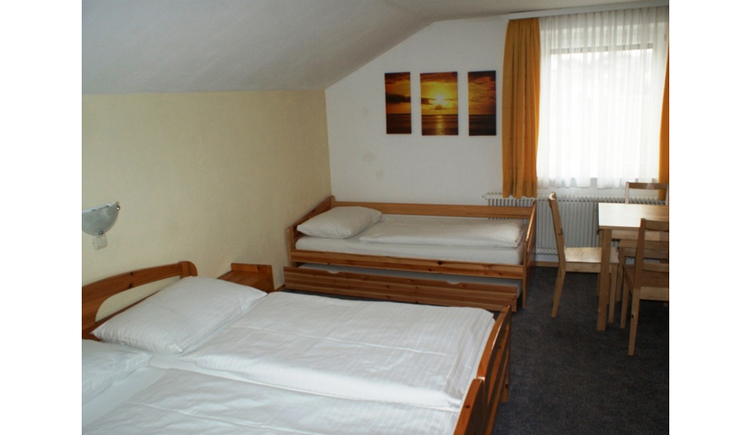 Bedroom with double bed, single bed, in the background a window, pictures on the wall, chair