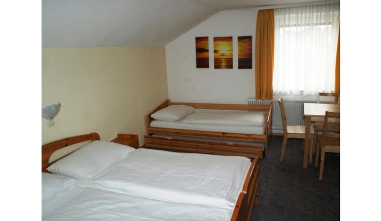 Schlafzimmer mit Doppelbett, Einzelbett, im Hintergrund ein Fenster, Bilder an der Wand, seitlich im Hintergrund ein Tisch mit Stühlen