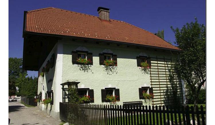Blick auf das Haus, mit Blumen bei den Fenster, im Vordergrund ein Zaun. (© Tourismusverband MondSeeLand)