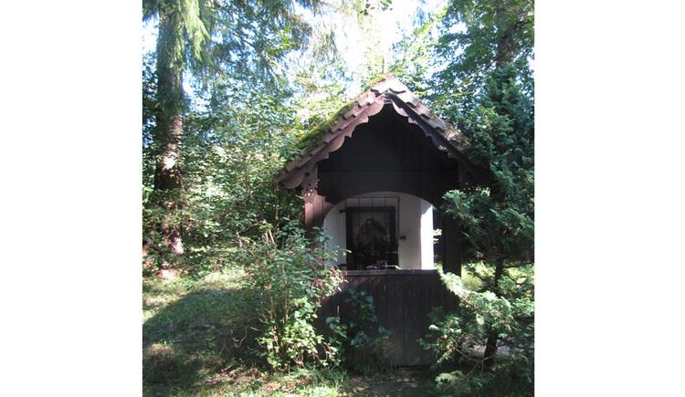 Blick auf die Kapelle, im Hintergrund ein Wald