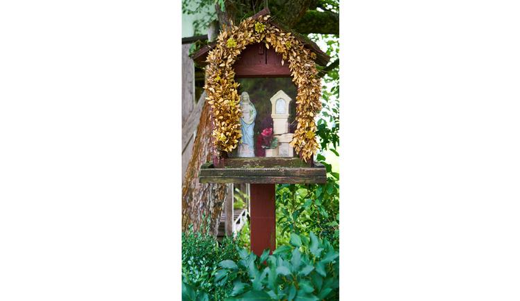 Blick auf den Bildstock mit Marienstatue und Blumen