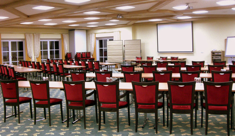 chairs and tables in front of a screeen and flipcharts. (© Eichingerbauer)