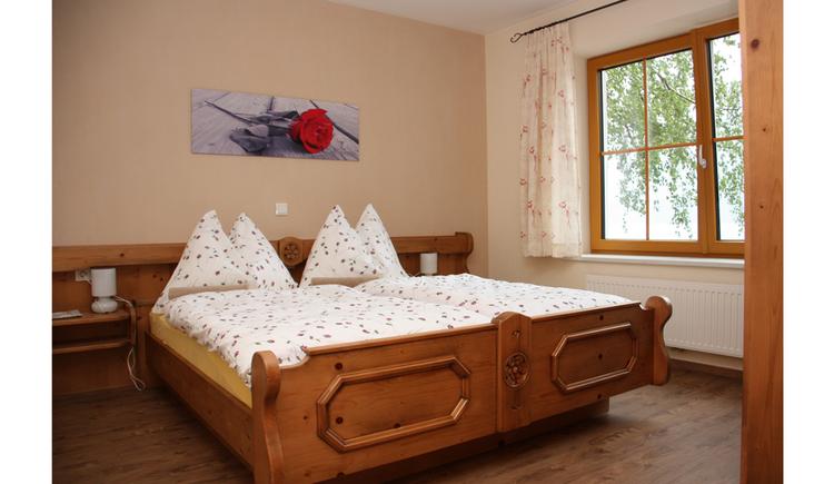Schlafzimmer mit Doppelbett, seitlich ein Fenster