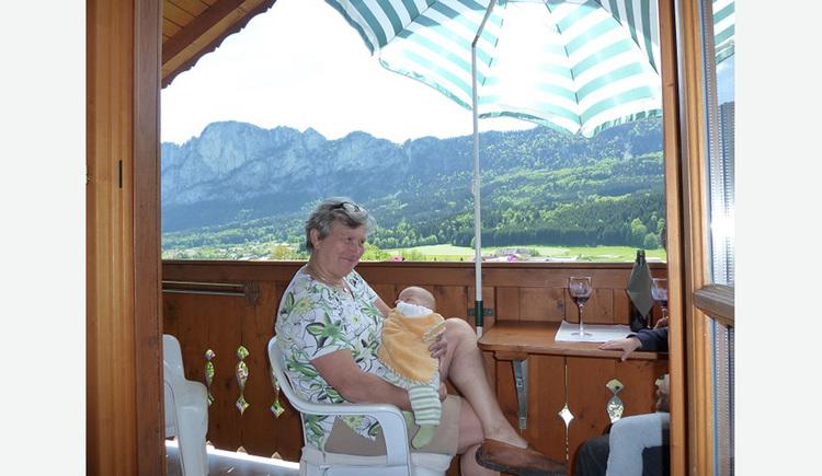 Person sitzt mit einem Baby auf dem Balkon unter einem aufgespannten Sonnenschirm