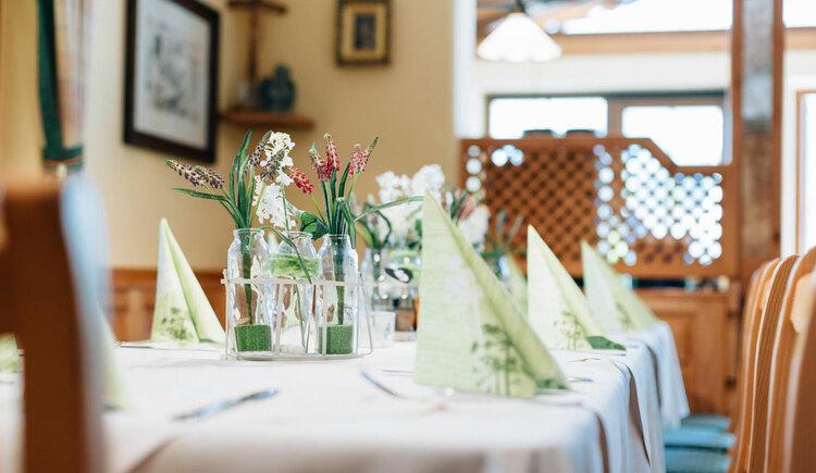 gedeckter Tisch mit Servietten und Blumen. (© Aichingerwirt)