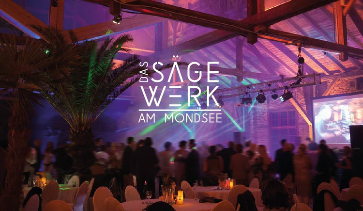 Photographing of an event with covered tables, palms, screen, people blurred in the background