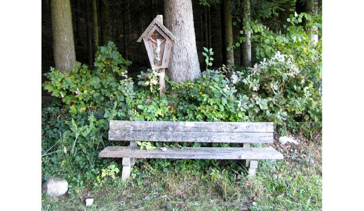 Blick auf ein Holzbankerl, im Hintergrund ein Marterl, Bäume
