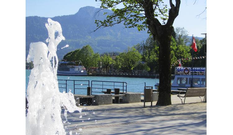 Blick von der Seepromenade  auf den See, Berge, seitlich der Springbrunnen