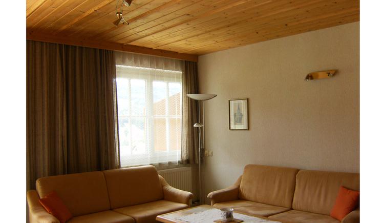 Wohnbereich mit Couch, Tisch, Stehlampe, im Hintergrund seitlich ein Fenster