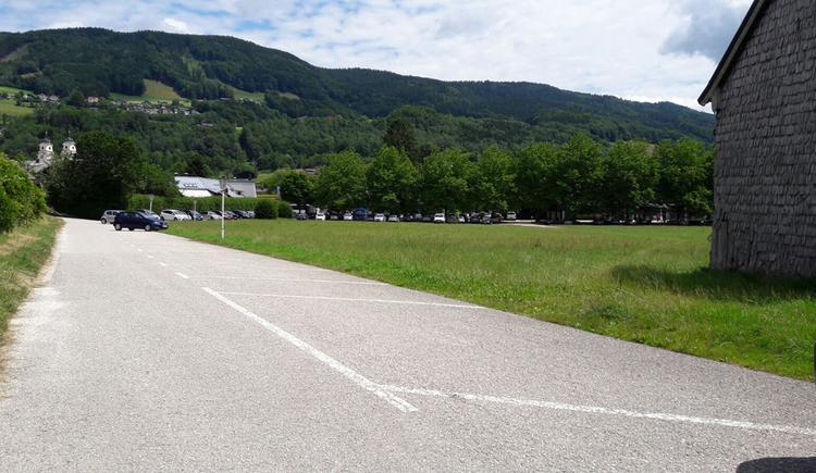Blick auf den Parkplatz, seitlich Wiesen, im Hintergrund Bäume