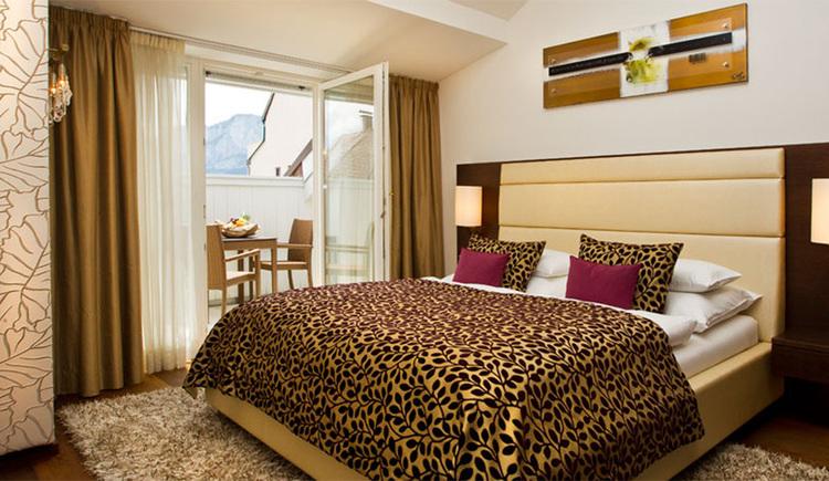 Schlafzimmer mit Doppelbett, Blick auf den Balkon mit Tisch und Stühlen