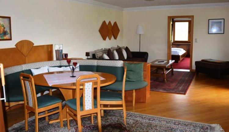 Wohnbereich, mit Eckbank, Tisch und Stühle, dahinter eine Couch, im Hintergrund eine offene Tür mit Blick ins Schlafzimmer