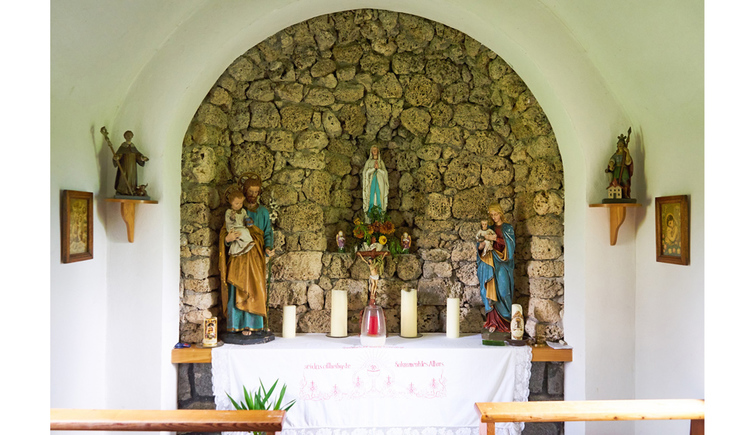 Blick auf den Altar, darauf Kerzen Heiligenfiguren