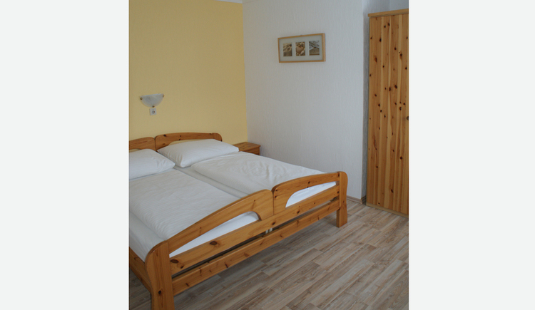 Bedroom with double bed, picture on the wall in the background