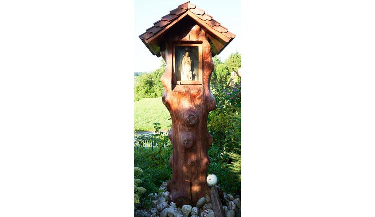 Blick auf das Holzbildstock, Marienstatue, im Hintergrund ein Garten