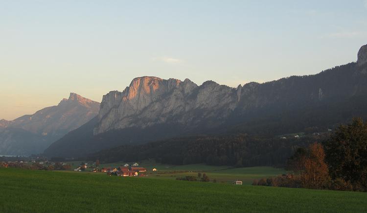 Eine Sonnenuntergangsszene. Von einem erhöhten Standpunkt aus Blick ins bereits schattige Tal unter der Drachenwand mit seinen Wiesen und Gehöften. Im Hintergrund die Drachenwand, deren oberstes Fünftel von den letzen Sonnenstrahlen bestrahlt wird. Links dahinter der noch im vollen Licht stehende Schafberg.