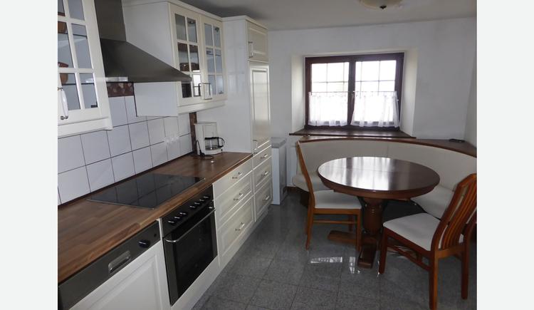 Küche mit Herd, Eckbank, Tisch und Stühle, im Hintergrund ein Fenster
