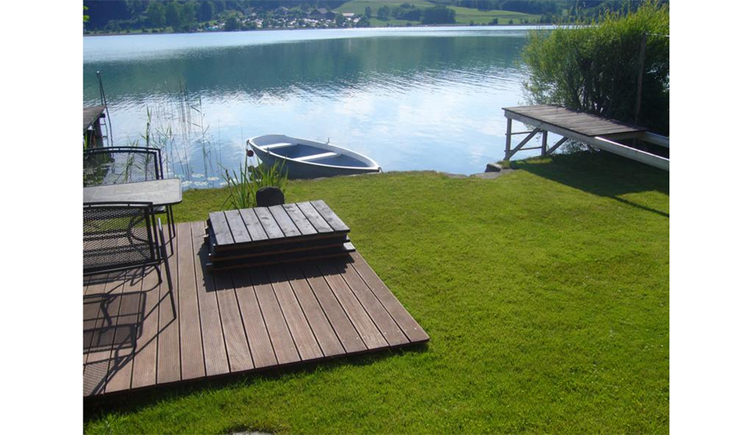 Wooden terrace, meadows, rowing boat in the lake
