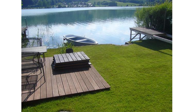 Holzterrasse, Wiesen, Ruderboot im See