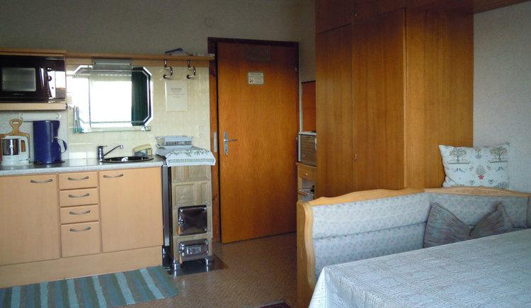 im Hintergrund die Küche mit Wasserkocher, Kaffeemaschine, Mikrowelle, Spüle, kleiner Ofen mit Holz zum Heizen, Kleiderschrank, im Vordergrund eine Eckbank, Tisch