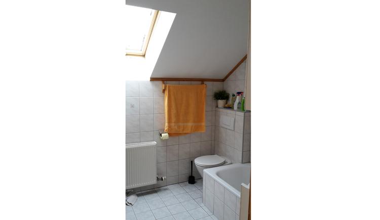 Badezimmer mit Toilette, seitlich ein kleiner Teil von der Badewanne, Dachfenster