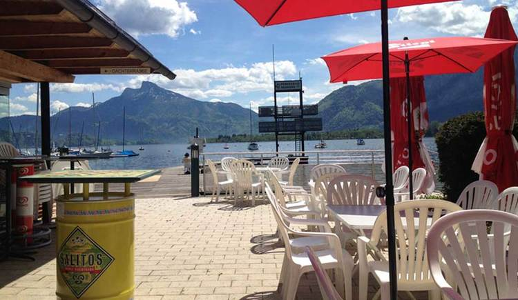 look from the terrace, with tables and chairs, the lake, in the Background the Schafberg\n