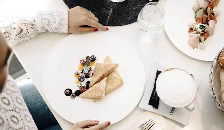 gedeckter Frühstückstisch mit Gebäck, Schinken, Tomaten, Käse, Gurken, Kaffee und süßen Köstlichkeiten