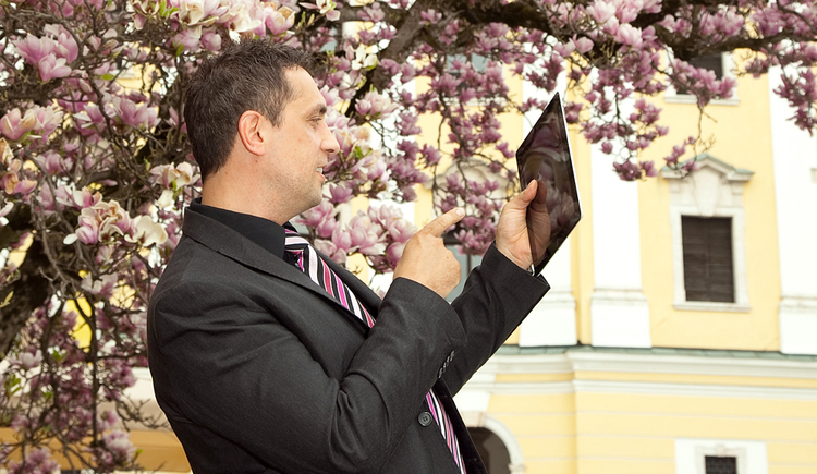 Person with a tablet, in the Background a tree\n
