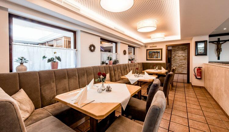 Gastzimmer, Bänke, Stühle und gedeckte Tische. (© Hotel Krone)