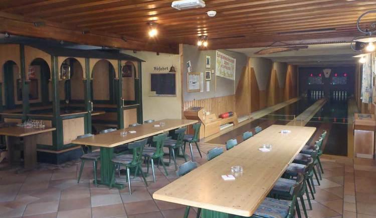 Innenbereich mit Tischen und Stühlen, im Hintergrund die zwei Kegelbahnen