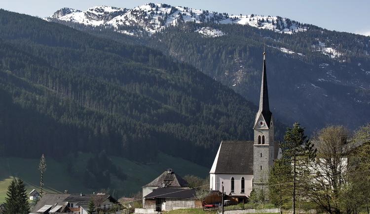 Katholische Kirche in Gosau vor einem überwältigendem Bergpanorama.