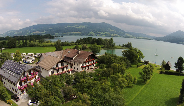 Aerial view: houses, trees, landscape, in the background the lake and the mountains