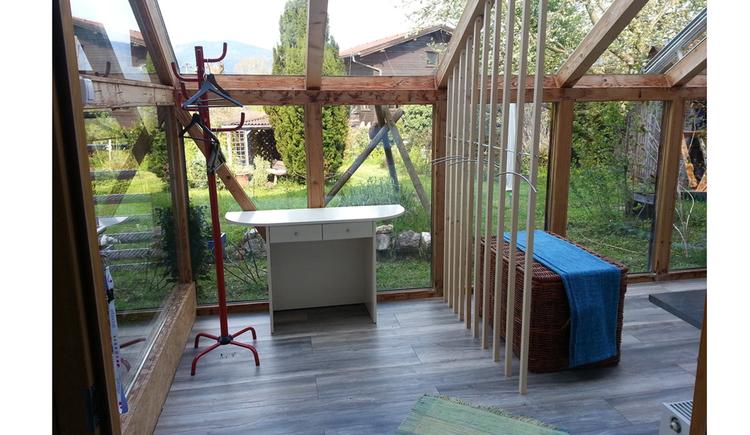 Wintergarten mit Tisch und Garderobenständer und Blick in den Garten