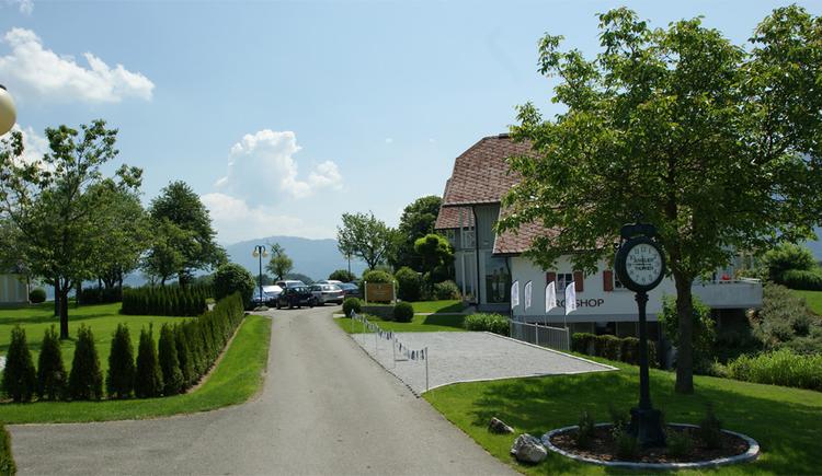 Blick auf die Einfahrt, im Vordergrund seitlich eine große Standuhr, Wiesen, Hecke, seitlich im Hintergrund das Haus, parkende Autos und die Berge