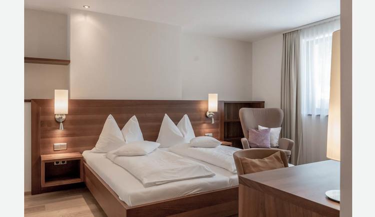 Doppelbett, Nachtkästchen, Lampen, gemütlicher hoher Sessel, seitlich ein Fenster