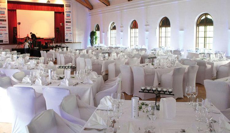 Festsaal im Veranstaltungszentrum SALA Schloss Mondsee mit runden, festlich geschmückten Tischen und dazu passenden Stühlen. (© Sala Schloss Mondsee)