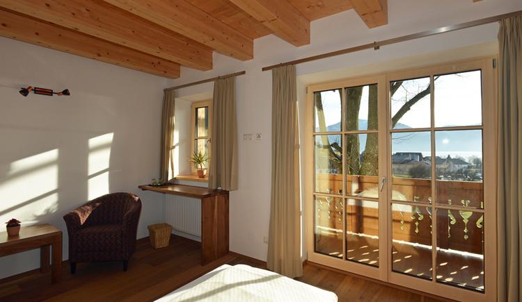 Doppelbett, kleine Sitzecke und Blick durchs Fenster auf den Balkon