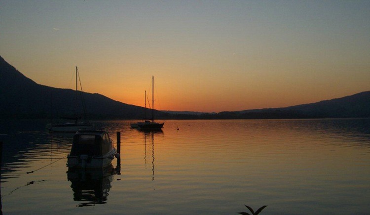 sunset at the lake, boats, mountains\n
