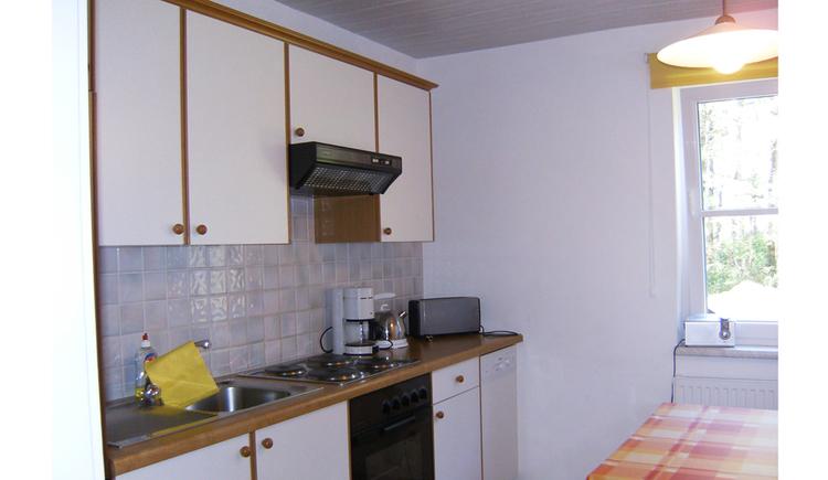 Küche mit Spüle, Herd, Kaffeemaschine, Wasserkocher, Toaster