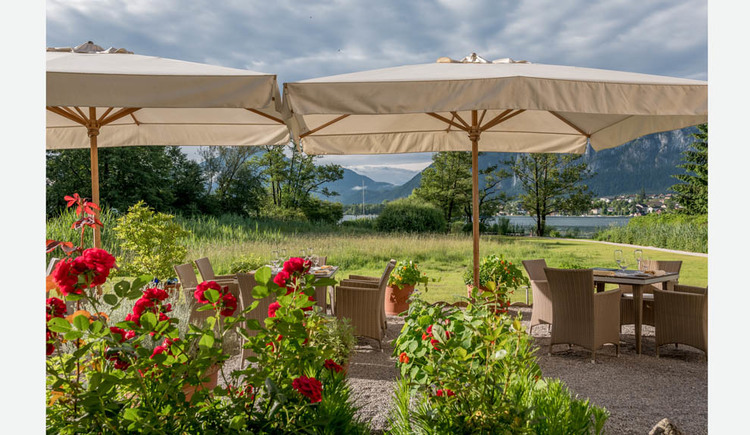 In the front rose bushes, behind it armchairs, set tables with glasses, umbrellas, in the background a meadow, trees, the lake and the mountains