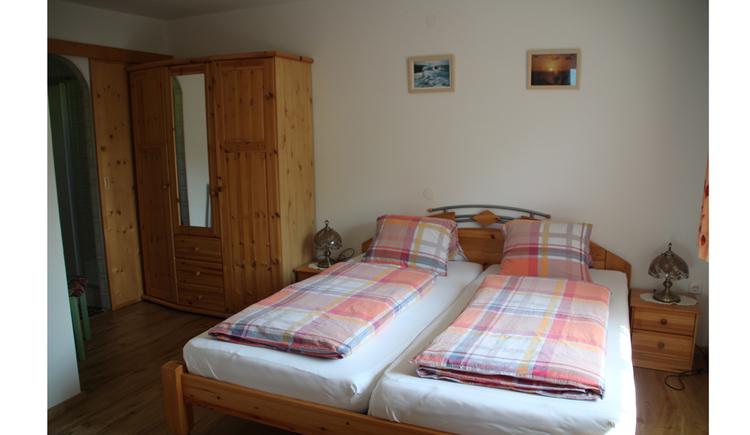 Doppelbett, Kleiderschrank, Bilder an der Wand