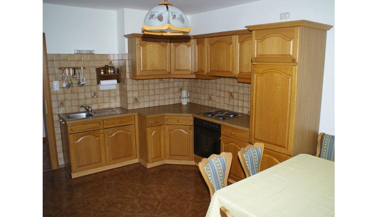 Küche mit Spüle, Herd, im Vordergrund Tisch und Stühle